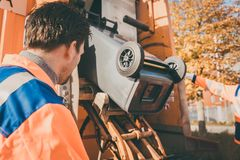 Worker emptying dustbin into waste vehicle stock images