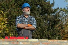 Worker examining brick wall at construction site. Worker or engineer control brick wall using level tool, real people, no retouch Royalty Free Stock Photo