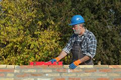 Worker with helmet examining brick wall. Worker or engineer control brick wall using level tool, real people, no retouch Stock Photos