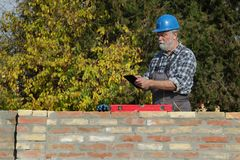 Worker examining brick wall at construction site. Worker or engineer control brick wall using level tool and tablet, real people, no retouch Stock Photography