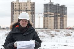 Worker or engineer holding drawing in hands and reading it on background of new apartment buildings and construction Stock Photo