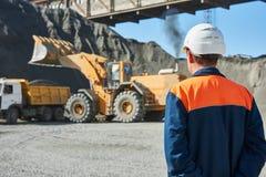 Worker Engineer looks on wheel loader loading truck stock image