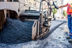 Worker or engineer operating an ashphalt paving machine Stock Images