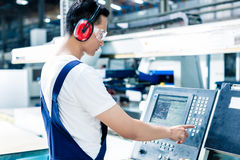 Worker entering data in CNC machine at factory Royalty Free Stock Photography