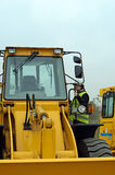 Worker entering excavator. Photo of worker entering excavator Stock Photos