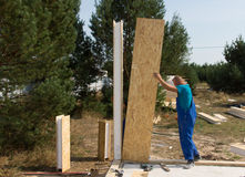 Worker erecting wall panels on a building site. Worker in overalls standing erecting insulated wooden wall panels on a building site of a new house Royalty Free Stock Photography