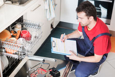 Worker estimating cost for broken dishwasher Royalty Free Stock Photography