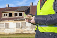 Worker with euro banknotes near abandoned house Royalty Free Stock Photography