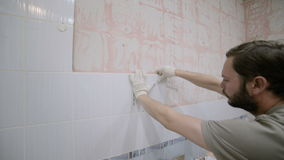 A worker of European appearance removes the old ceramic tile stock video footage