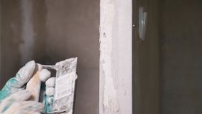 Worker evening concrete wall. Crop man evening wall with plaster and palette working in empty apartment under construction stock footage