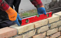 Worker examining brick wall. Worker control brick wall using level tool, selective focus, real people Royalty Free Stock Photos