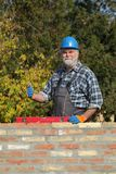 Worker examining brick wall and gesturing. Smiling worker control brick wall using level tool with thumb up Stock Image