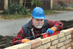 Worker examining brick wall using level tool. Worker control brick wall using level tool, real people, no retouch Stock Image