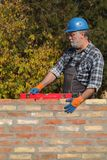Worker examining brick wall using level tool. Worker control brick wall using level tool, real people, no retouch Stock Photography