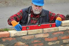 Worker examining brick wall. Worker control brick wall using level tool, real people, no retouch Royalty Free Stock Image