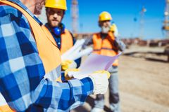 Worker examining a building plan while standing at construction site. With colleagues stock photography