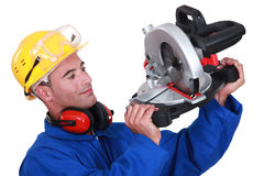 Worker examining his circular saw. Stock Photo