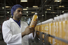 Worker examining orange juice bottle at bottling plant Royalty Free Stock Image