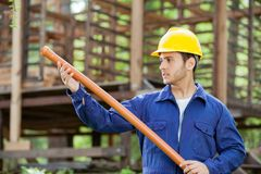 Worker Examining Pipe At Construction Site Stock Photo