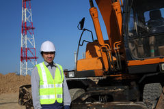 Worker with excavator. Worker standing with excavator on location site Stock Photo