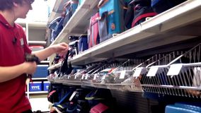 Worker exhibiting goods and checking price stock video