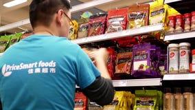Worker exhibiting seasoning for sale on display rack stock footage