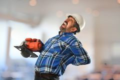 Worker Experiencing Back Injury. Hispanic worker experiencing back injury while working with circular saw royalty free stock image
