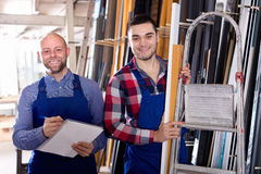 Worker at factory with boss. Worker operating in lathe, his boss with papers nearby royalty free stock photos