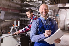 Worker at factory with boss. Positive worker operating in lathe, his boss with papers nearby royalty free stock photography