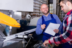 Worker at factory with boss. Smiling worker in coverall operating in lathe, his boss with papers nearby royalty free stock images