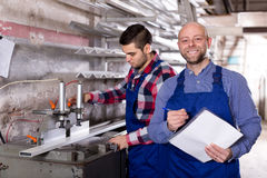 Worker at factory with boss. Smiling worker in uniform operating in lathe, his boss with papers nearby stock photo