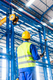 Worker in factory controlling crane with remote Royalty Free Stock Images