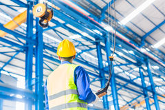 Worker in factory controlling crane with remote stock image