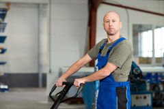 Worker in factory with hand lift Royalty Free Stock Photos