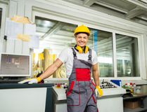 Worker on a factory. Happy worker wearing safety hat in a factory control room royalty free stock images
