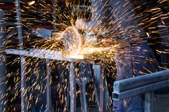 Worker Cutting Steel And making sparks fly. Worker in a factory is holding an electrical circular saw and cutting metal. There are also flying sparks on photo Royalty Free Stock Photography