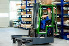 Worker in factory in lift truck Stock Images