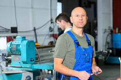 Worker in factory on the machine Royalty Free Stock Photography