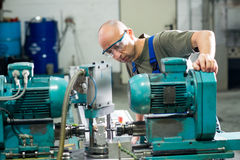 Worker in factory on the machine Stock Photography