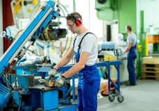 Worker in factory. Worker in protective clothing in factory using machine stock photo