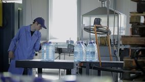 Worker at factory takes packed bottles of water from conveyor belt. stock video footage