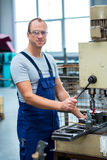Worker in factory using drill machine Stock Images