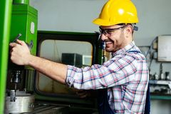 Worker in factory using drill machine stock image