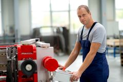 Worker in factory using machine Royalty Free Stock Photography