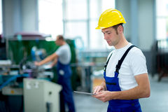 Worker in factory using tablet pc Stock Photo