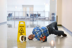 Worker Falling on Floor. Hispanic worker falling on wet floor crying in pain Stock Photography