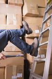 Worker falling off ladder in warehouse Stock Images