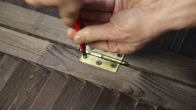 Worker is fastening the door hinge to the furniture detail using screwdriver.  stock footage