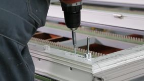 Worker fastens the accessories to plastic window. Worker fastens the fittings with a screwdriver to the plastic window in the shop for the production of plastic stock footage