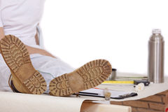 Worker with feet up on table. Resting - isolated on white background Royalty Free Stock Image